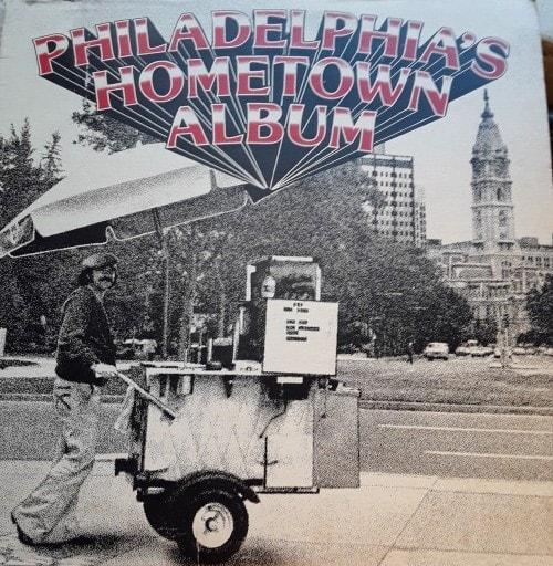 album cover featuring a street food vendor walking on a Philadelphia street.